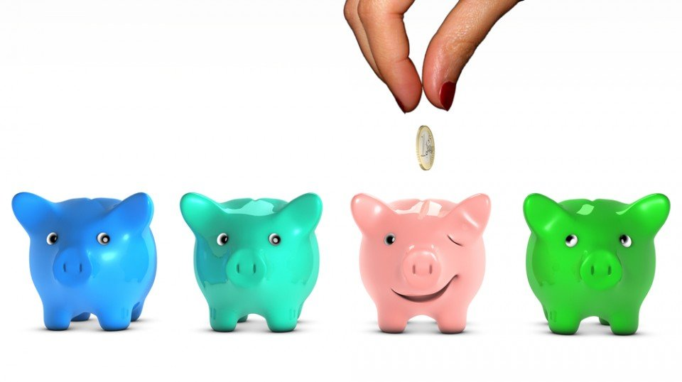 Four colored piggy banks with the pink one winking