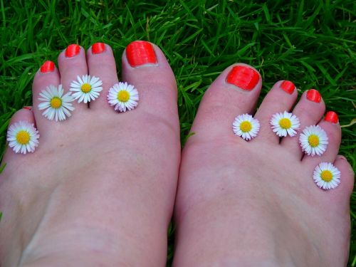 Brightly painted toe nails with flowers between toes