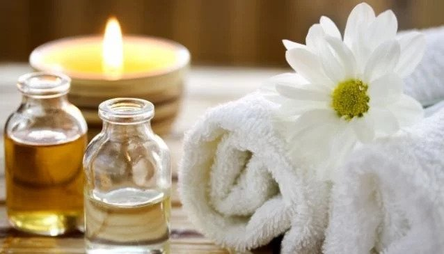 Oils, candle, flowers and towel at a spa