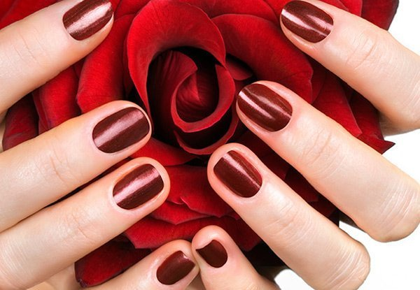 hands with red nails holding a red rose