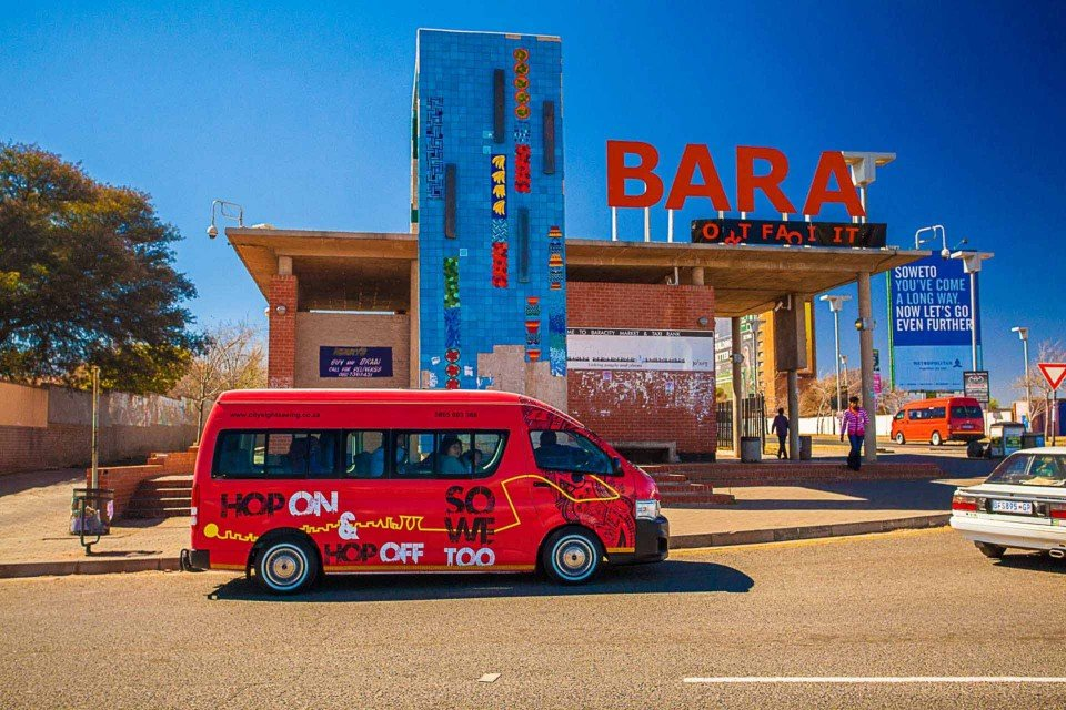 The City Sightseeing Joburg SO WE TOO red bus caught from Gold Reef City in front of Bara sign