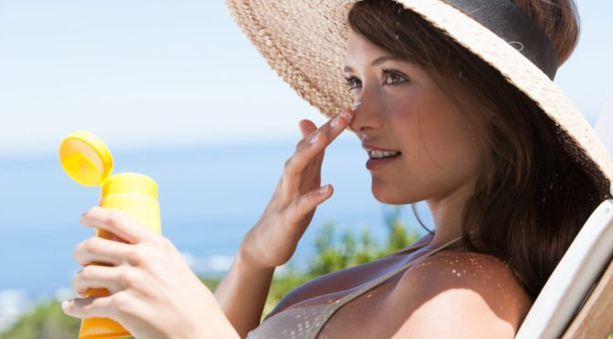 Woman applying sunscreen on face