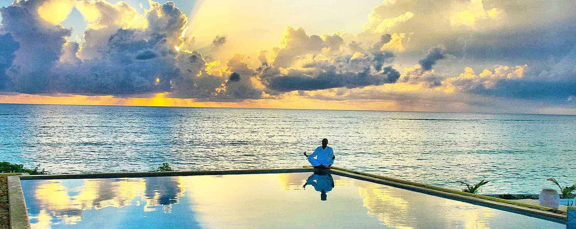 A man meditating by the pool at Kasha Boutique Hotel found through Booking.com