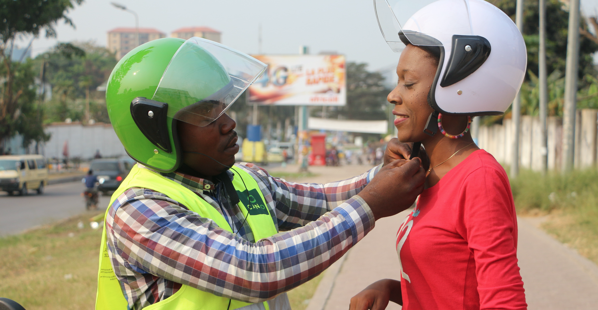 A CanGo Driver helps a passenger put her helmet on