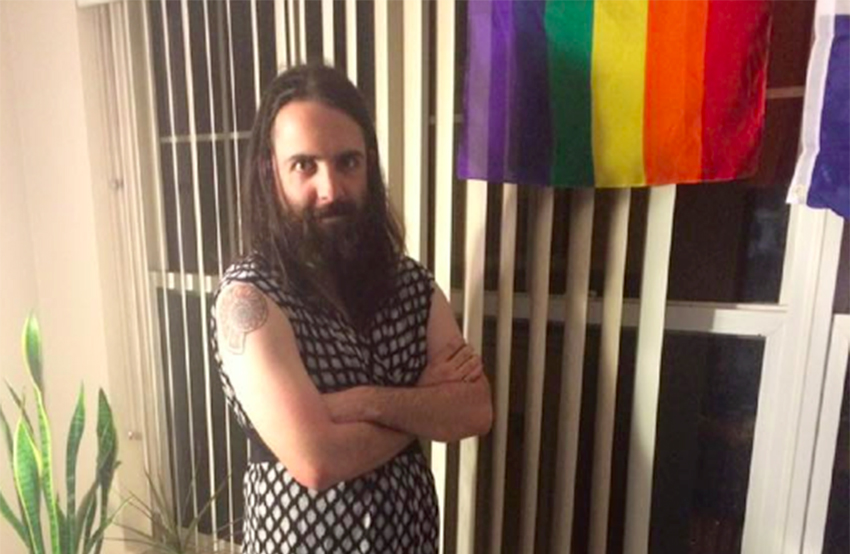 A bearded man in a dress with gay pride flag