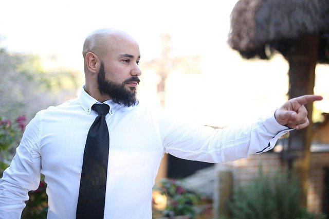 Bald headed man with a beard in a white shirt and tie